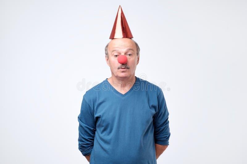 Zmieszany mężczyzna na błazenu kapeluszu spojrzeniach z wahającym wyrażeniem obrazy royalty free