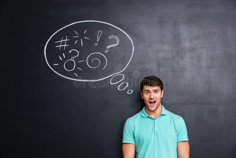 Zmieszany mężczyzna myśleć o problemu z blackboard za on zdjęcie stock