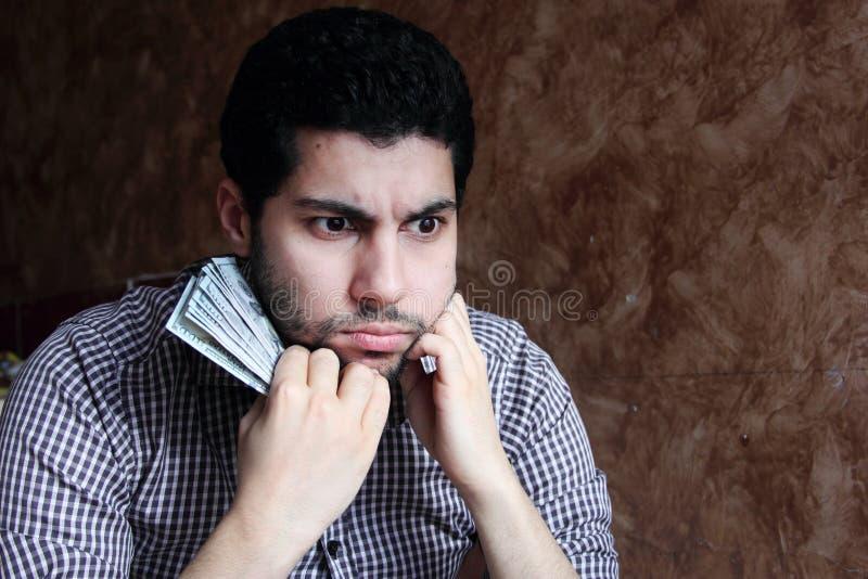 Zmieszany smutny arabski młody biznesmen z dolarowym rachunkiem obraz stock