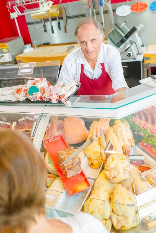 Zmniejszający się widok masarki porci klient obraz stock