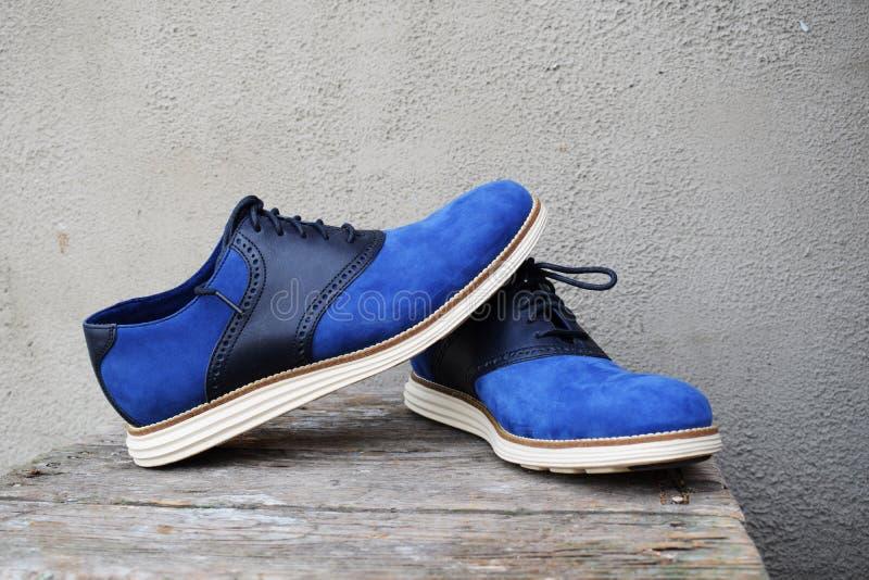 Zmrok - błękitni sneakers z białą podeszwą na drewnianym tle zdjęcie royalty free