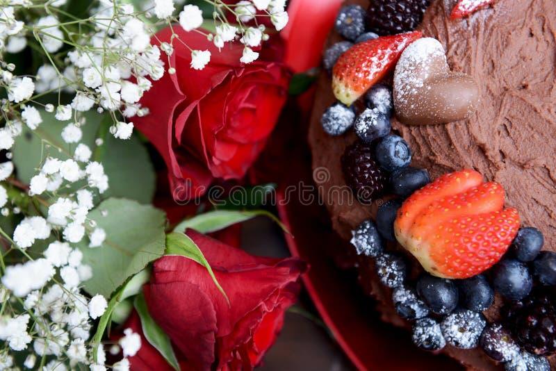 Zmrok czerwone róże i Czekoladowy tort z jagodami - zdjęcia royalty free