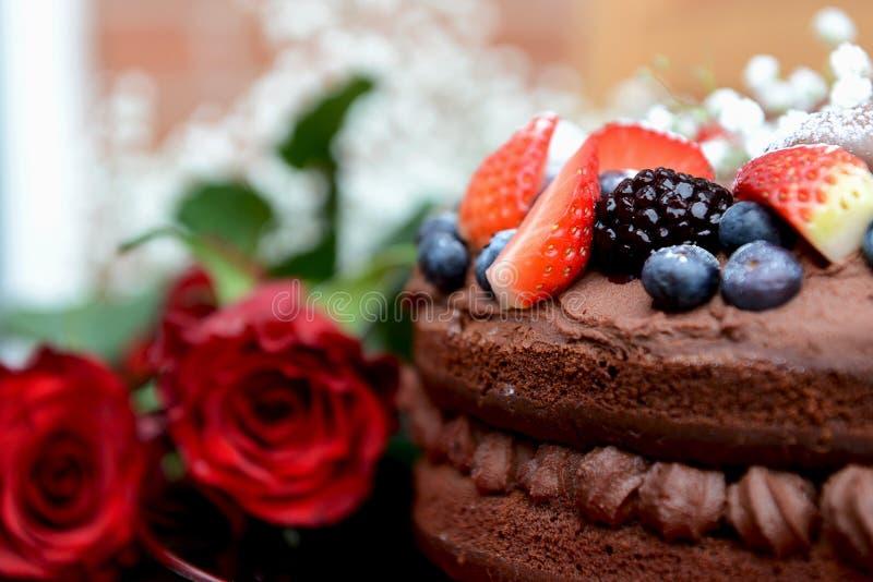 Zmrok czerwone róże i Czekoladowy tort z jagodami - obrazy stock