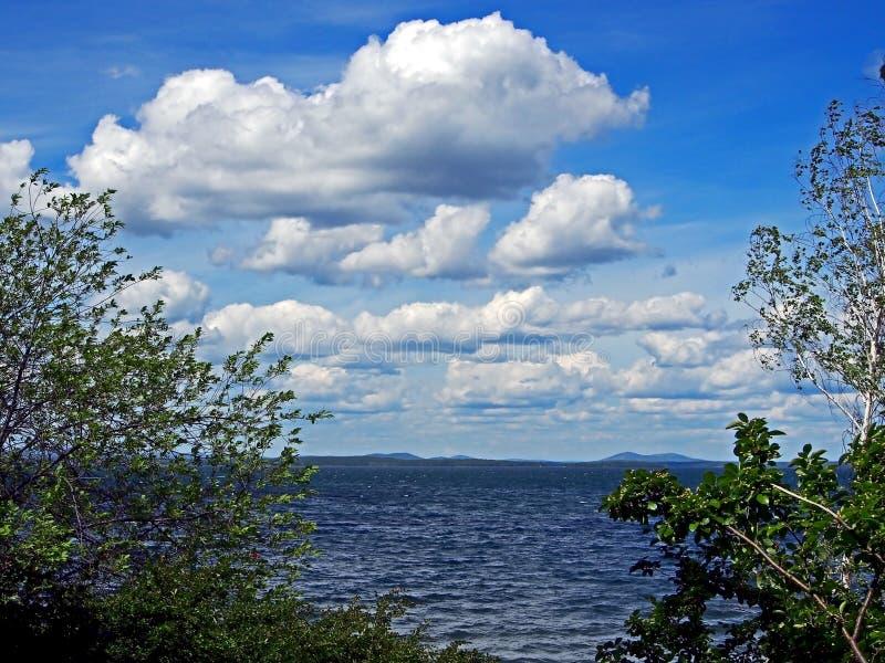 Zmrok - niebieskie niebo z białymi cumulonimbus chmurami nad ranku jeziorem obrazy stock