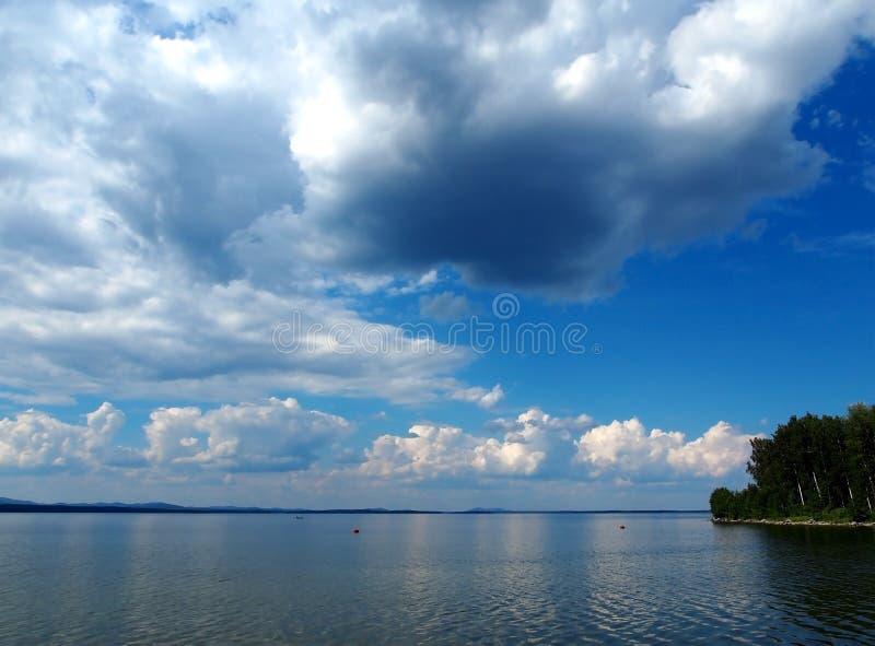 Zmrok - niebieskie niebo z białymi cumulonimbus chmurami nad ranku jeziorem zdjęcie stock