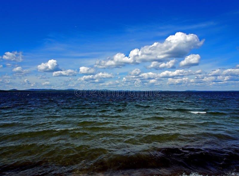 Zmrok - niebieskie niebo z białymi cumulonimbus chmurami nad ranku jeziorem obraz stock