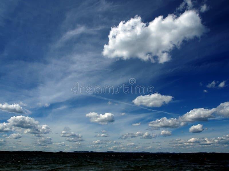 Zmrok - niebieskie niebo z białymi cumulonimbus chmurami nad ranku jeziorem fotografia stock