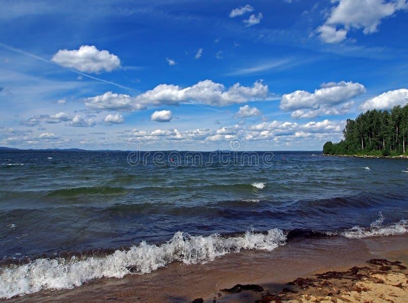 Zmrok - niebieskie niebo z białymi cumulonimbus chmurami nad ranku jeziorem fotografia royalty free