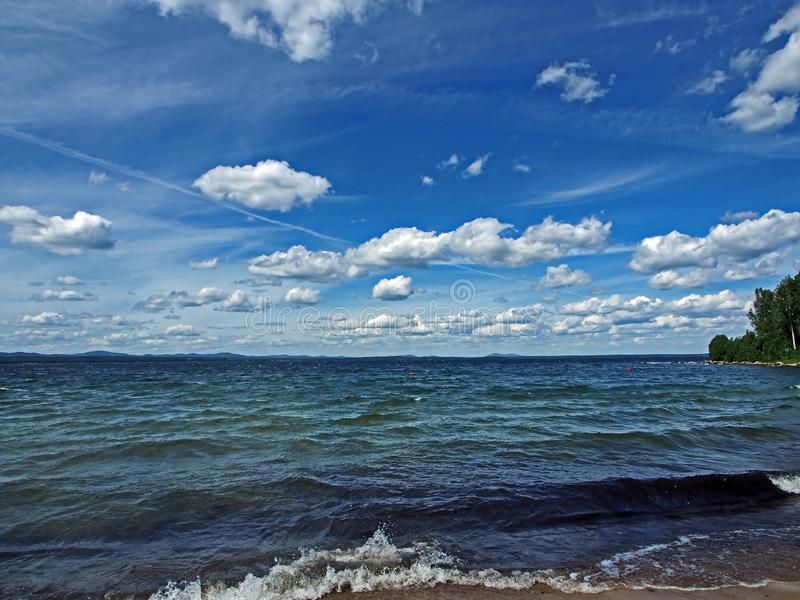 Zmrok - niebieskie niebo z białymi cumulonimbus chmurami nad ranku jeziorem obraz royalty free