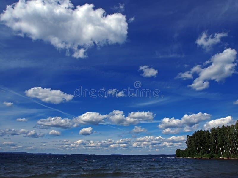 Zmrok - niebieskie niebo z białymi cumulonimbus chmurami nad ranku jeziorem zdjęcia stock