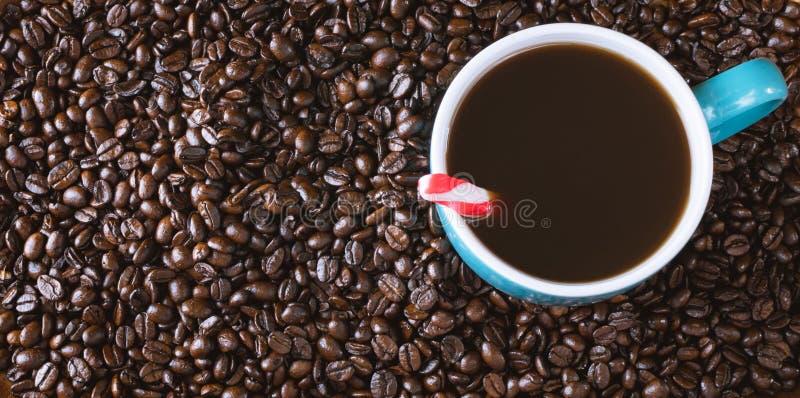 Zmrok piec kawowych fasoli tło z błękit wypełniającą filiżanką z miętówką zdjęcie stock