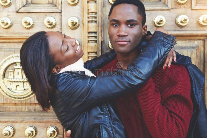Zmrok skinned pary ma zabawę podczas gdy stojący outdoors przeciw rocznika drzwi, dwa przyjaciela cieszy się rekreacyjnego czas fotografia royalty free