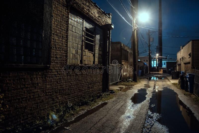 Zmroku, krupiastej i mokrej przemysłowa miasto aleja przy nocą, obraz stock