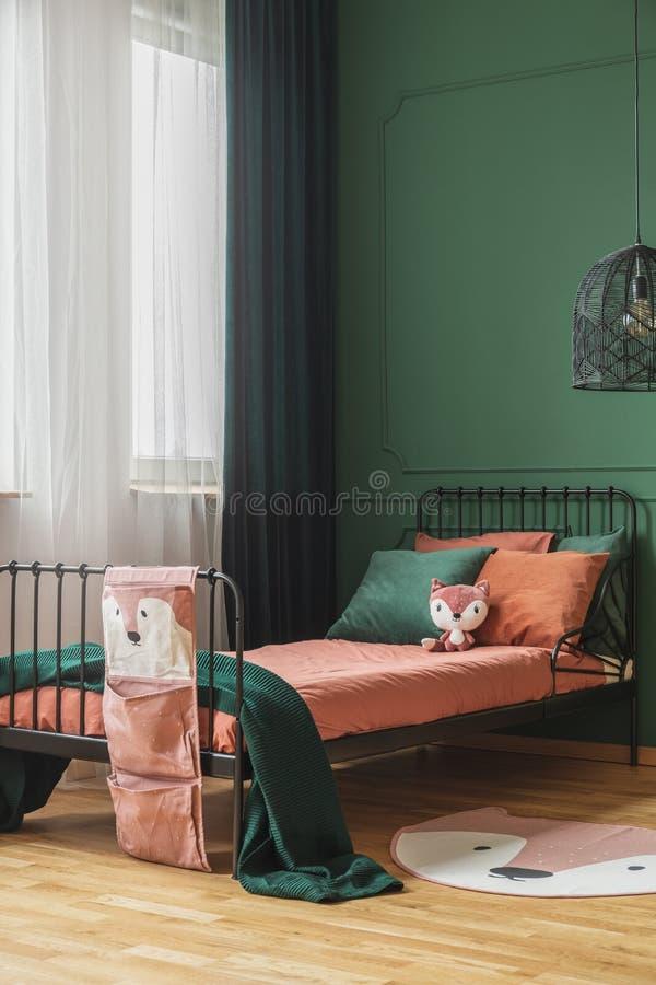 Zmroku - pomarańczowej i szmaragdowej zieleni poduszki na pojedynczym metalu łóżku w modnej nastolatek sypialni obraz stock