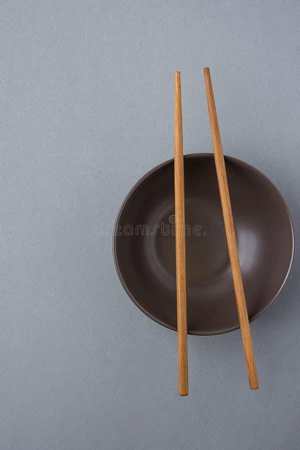 Zmroku Pusty puchar z Brown Bambusowymi Chopsticks na Popielatym tle Japońska Chińska Azjatycka kuchnia zdjęcie stock