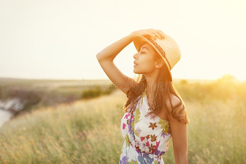 Zmysłowa młoda kobieta w słomianym kapeluszu w świetle słonecznym zdjęcie royalty free
