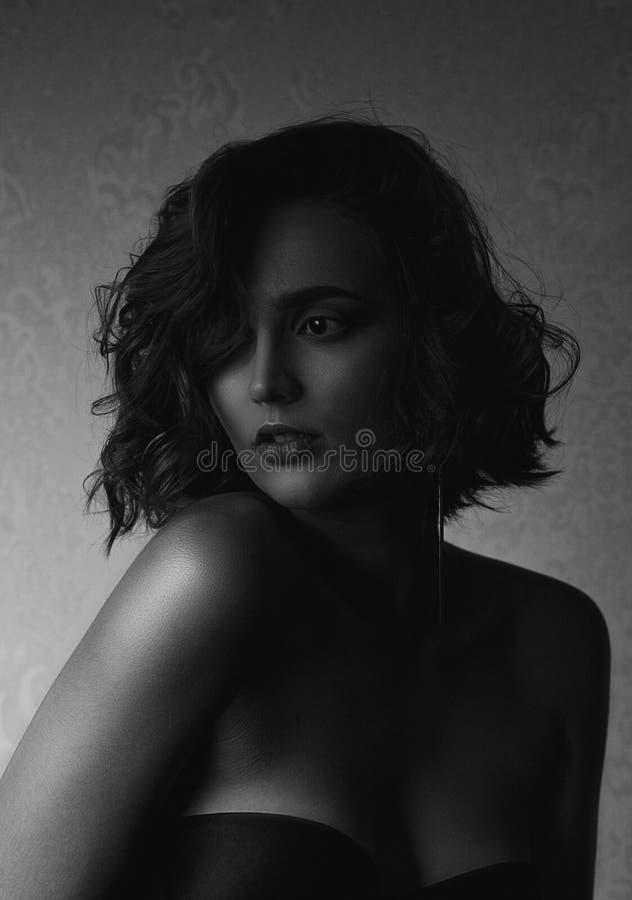 Zmysłowy brunetka model z kędzierzawym włosy i nagimi ramionami pozuje z kontrasta światłem, Czarny i biały fotografia zdjęcia royalty free