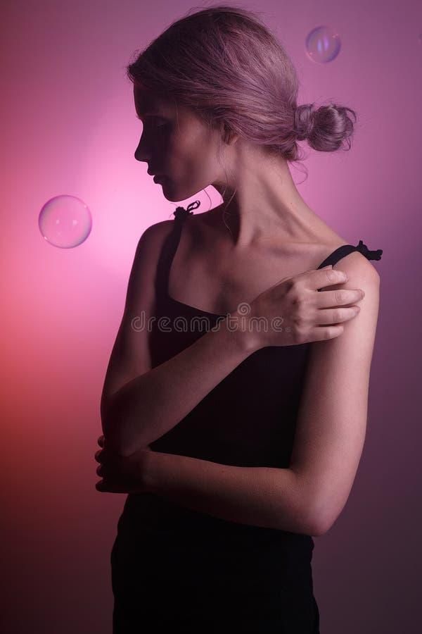 Zmysłowa caucasian dziewczyna w czerni sukni, cień na jej twarzy na różowym tle Dwa mydlanego bąbla latają wokoło jej głowy zdjęcia stock