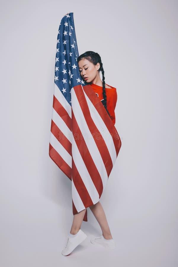 Zmysłowa elegancka azjatykcia dziewczyna z zamkniętymi oczami zawijającymi w flaga amerykańskiej i stanging odizolowywającym na p fotografia stock