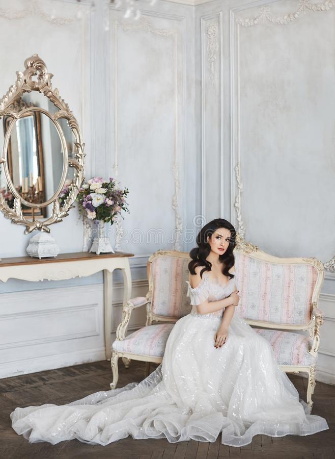 Zmysłowa i piękna brunetka modela dziewczyna z jaskrawym makeup w modnej koronki sukni z nagimi ramionami siedzi na zdjęcie stock