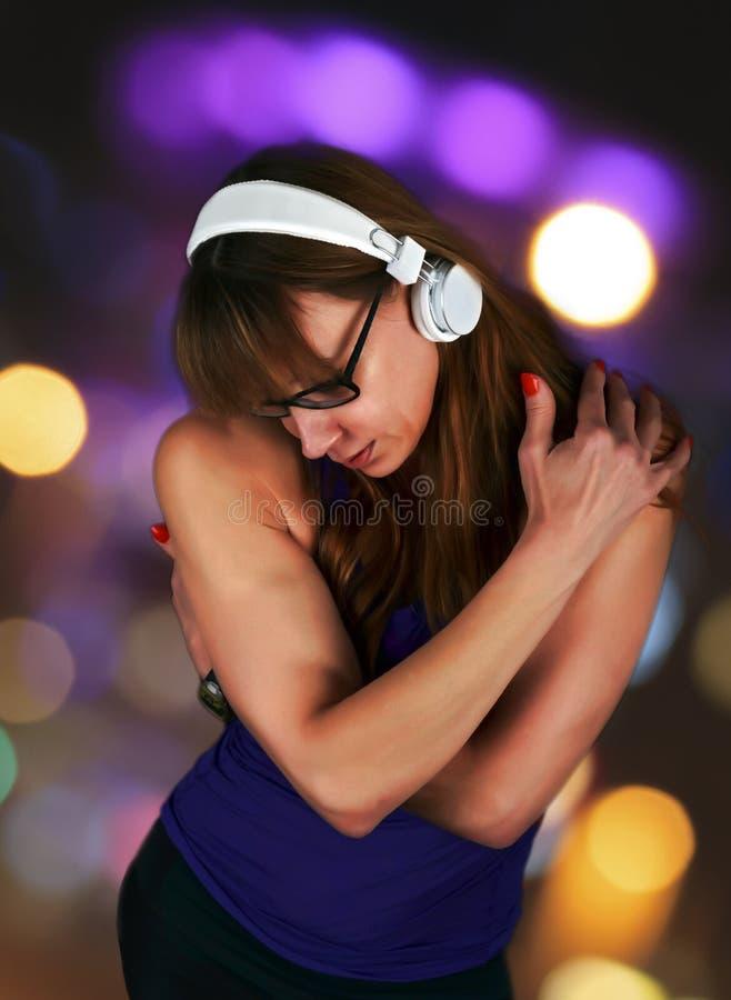 Zmysłowa kobieta gubjąca w słuchaniu muzyczny przytulenia herselff zdjęcie royalty free