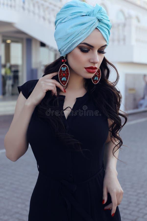 Zmysłowa kobieta jest ubranym eleganckiego czerń smokingowego i jedwabniczego turban zdjęcia stock