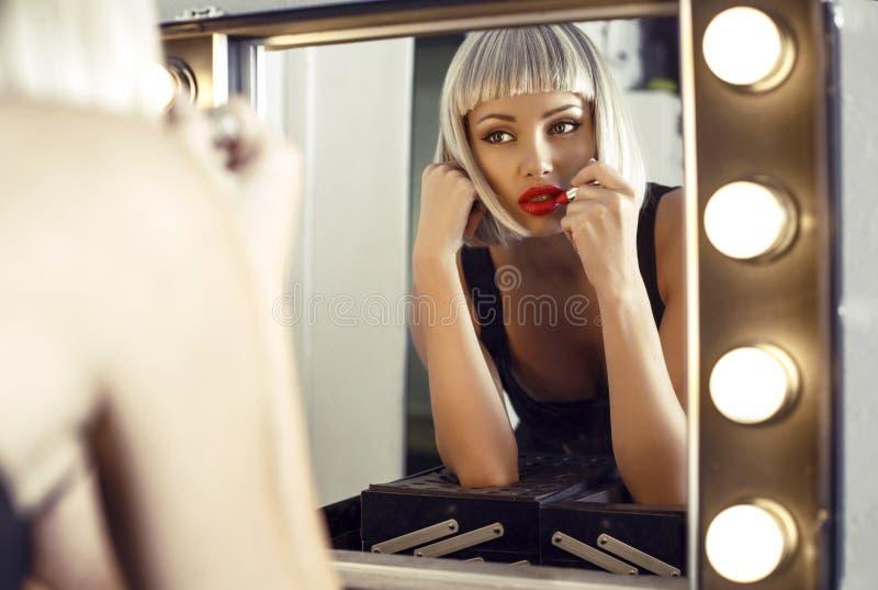 Zmysłowa kobieta w blond peruce robi makeup w przebieralni zdjęcia stock