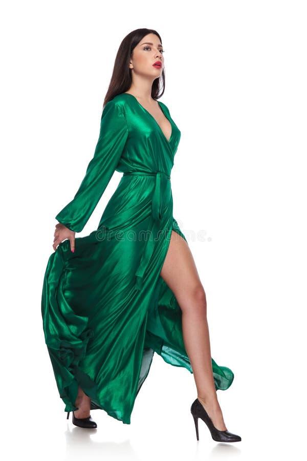 Zmysłowa kobieta w trzepotliwej długiej zieleni ubierającej chodzi strona obrazy royalty free