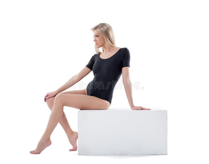 Zmysłowa młoda blondynka pozuje siedzieć na sześcianie zdjęcia stock