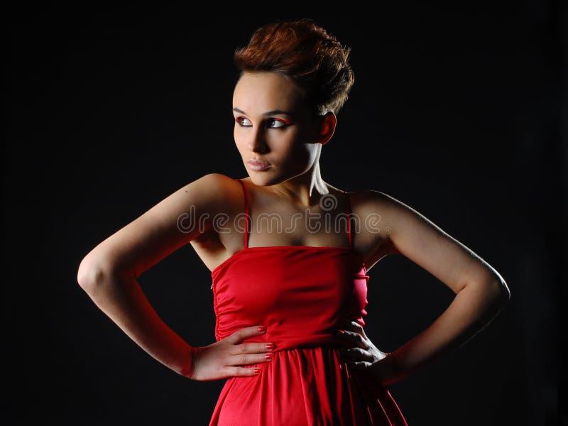 Zmysłowa młoda dama w czerwieni sukni pozuje studio piękna pojęcia mody ikony ustalona sylwetki kobieta zdjęcia stock