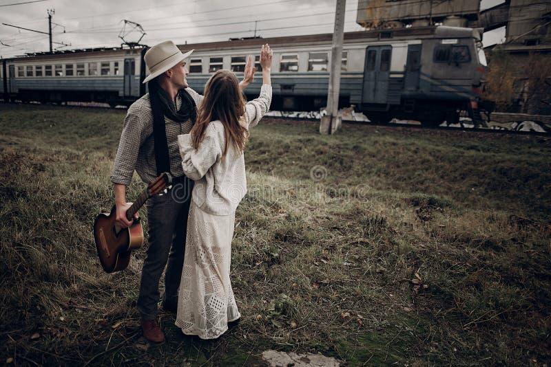 Zmysłowa modniś para, gypsy kobieta w boho odzieżowym i muzyk, zdjęcie royalty free