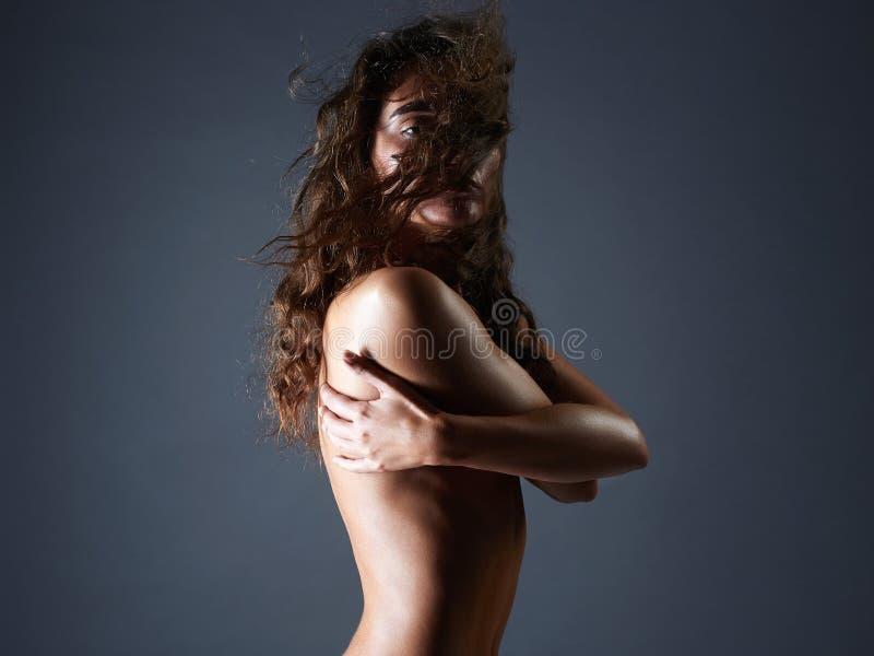 Zmysłowa naga dziewczyna z kędzierzawym latającym włosy fotografia stock