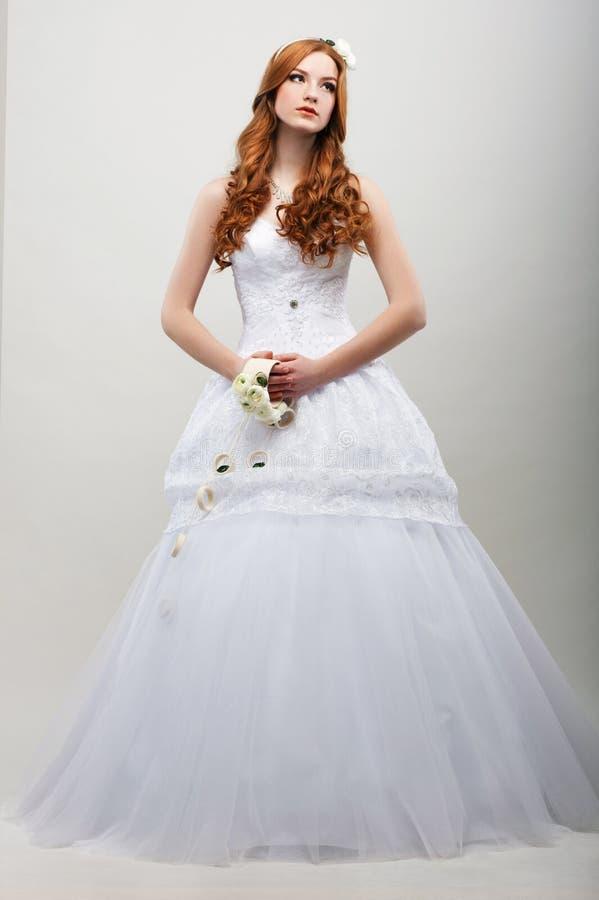 Zmysłowość. Romantyczna narzeczona w biel Długiej sukni z bukietem kwiaty zdjęcia royalty free