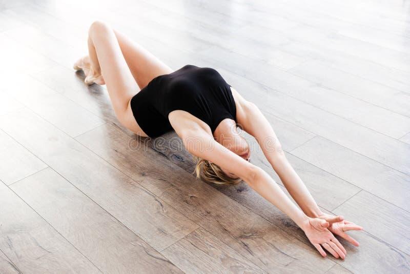 Zmysłowy młodej kobiety baleriny lying on the beach i rozciąganie na podłoga obraz royalty free
