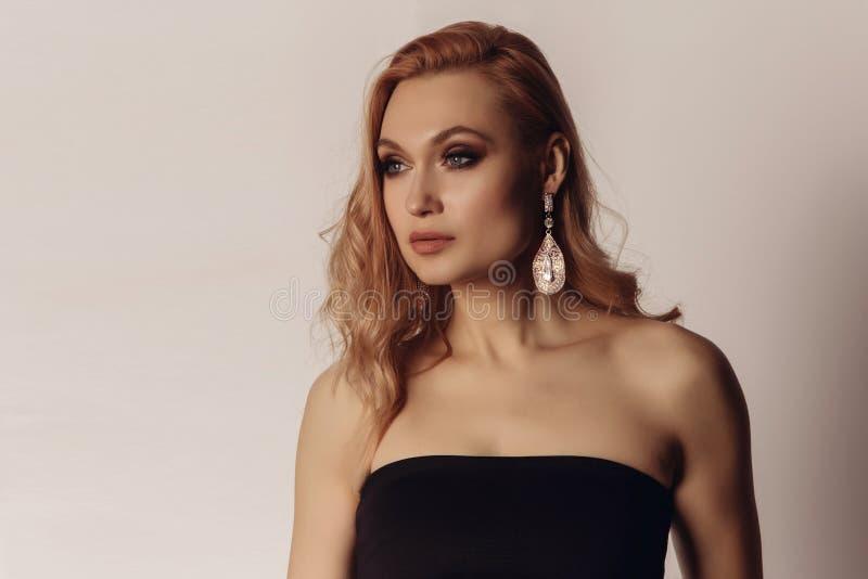 Zmysłowy portret bardzo atrakcyjna blond kobieta z kreatywnie włosianym stylem i duży moda kolczyk z czerń wierzchołkiem fotografia royalty free