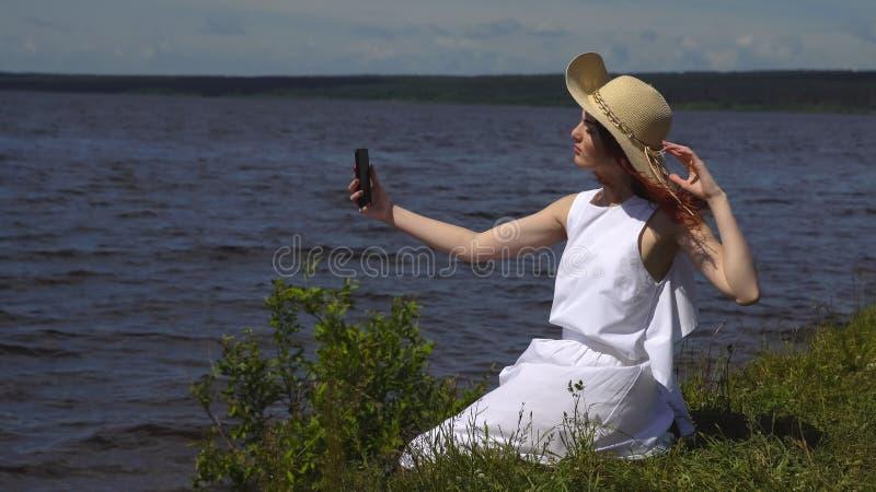 Zmysłowy zakończenie w górę portreta piękna dziewczyna w lato bielu sukni na rzece dziewczyna robi selfie outdoors na smartphone  obrazy royalty free