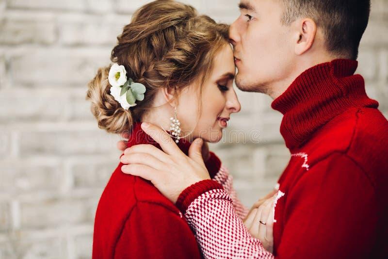 Zmys?owo?ci para w czerwonych pulowerach ma zabaw? wp?lnie, ?wi?tuj?cy nowego roku fotografia royalty free