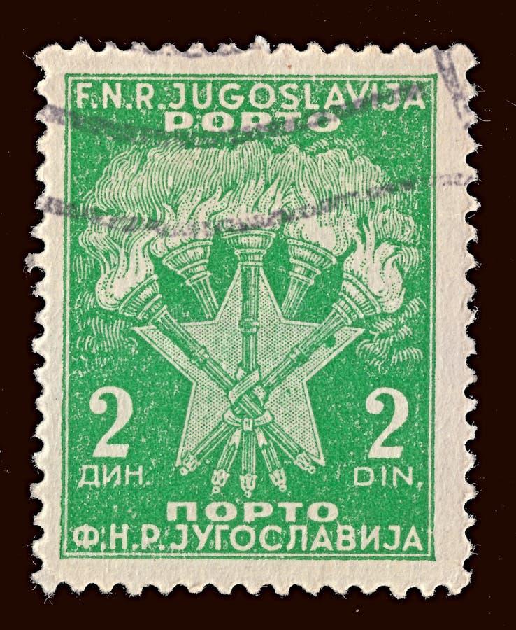 Znaczek drukujący w Jugosławia przedstawień rękach Podkłada ogień i gwiazdy, opłata pocztowa znaczków należny seria około 1946, obraz stock