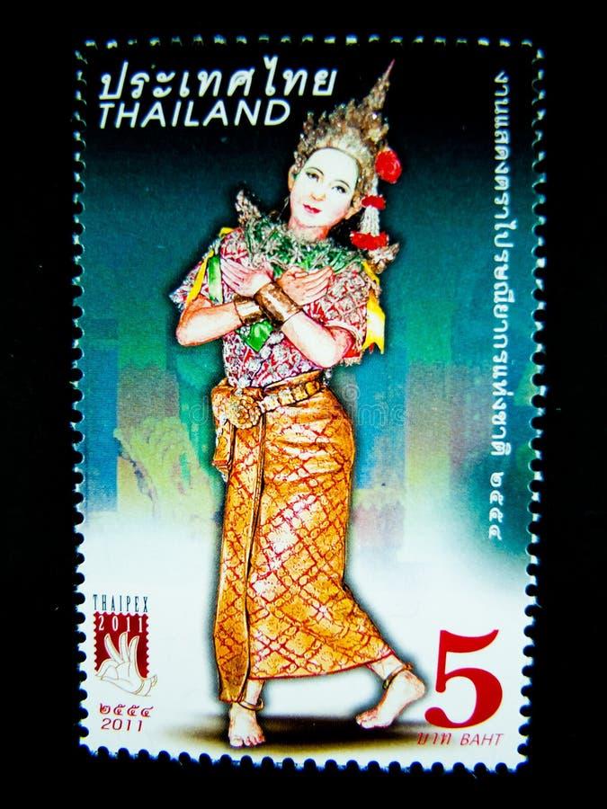 Znaczek drukujący w Tajlandia pokazuje wizerunek kobieta w Tajlandzkim muzykalnym ludowym dramata kostiumu dalej na wartości przy obrazy royalty free