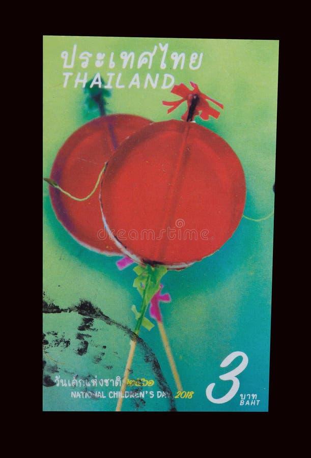 Znaczek drukujący w Tajlandia pokazuje wizerunek Tajlandzka czerwona stara tradycyjna dzieciak zabawka dla robić dźwięka huśtać s zdjęcia royalty free