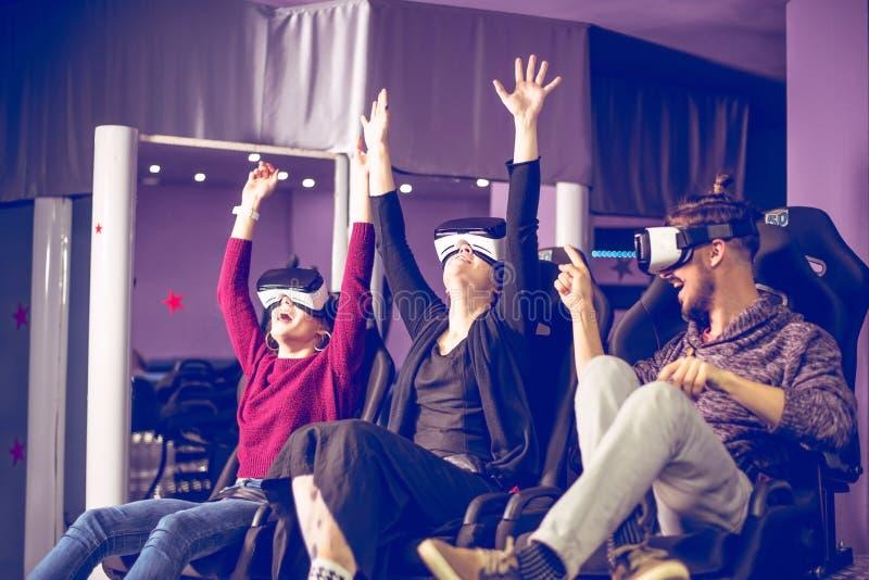 Znajomi w wirtualnych okularach oglÄ…dajÄ…cy filmy w kinie ze specjalnymi efektami w 5d zdjęcie royalty free