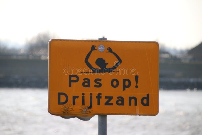 znak ostrzegawczy dla quicksand przy Hollandse IJssel brzeg rzeki zdjęcie royalty free