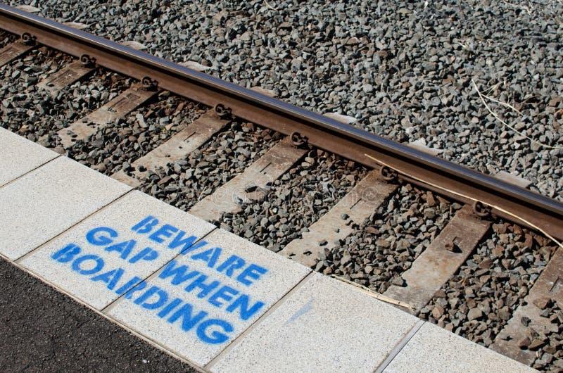 Znak ostrzegawczy przy stacją kolejową dla wystrzega się przerwę gdy wsiadający obraz na platformie zdjęcia royalty free