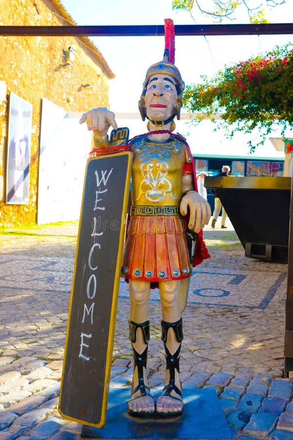 Znak Powitalny, Drewniana statua Romański żołnierz, podróż Portugalia, Faro śródmieście, Średniowieczny i Dziejowy, Śródziemnomor zdjęcie stock
