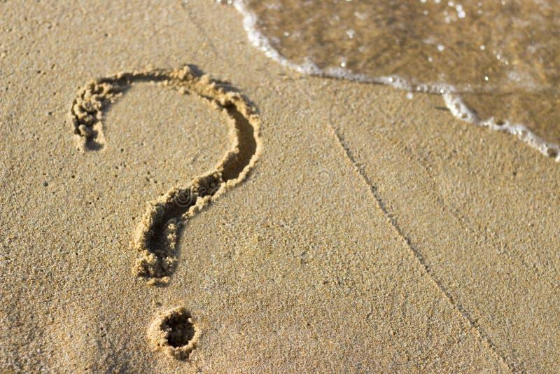 Znak zapytania rysujący na piaskowatej plaży i morze pienimy się, w górę, odgórny widok obraz royalty free