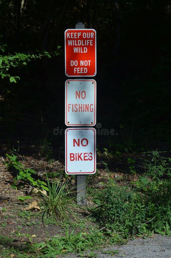3 znaka na jeden słupie: Utrzymuje Nasz przyrody Dzika Żadny Nie karma, Żadny połów, Żadny rowery zdjęcie stock