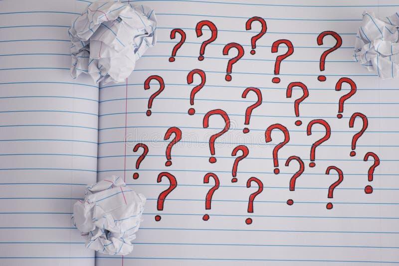 Znaki zapytania na notatnika prześcieradle z niektóre zmiętymi papierowymi piłkami zdjęcie royalty free