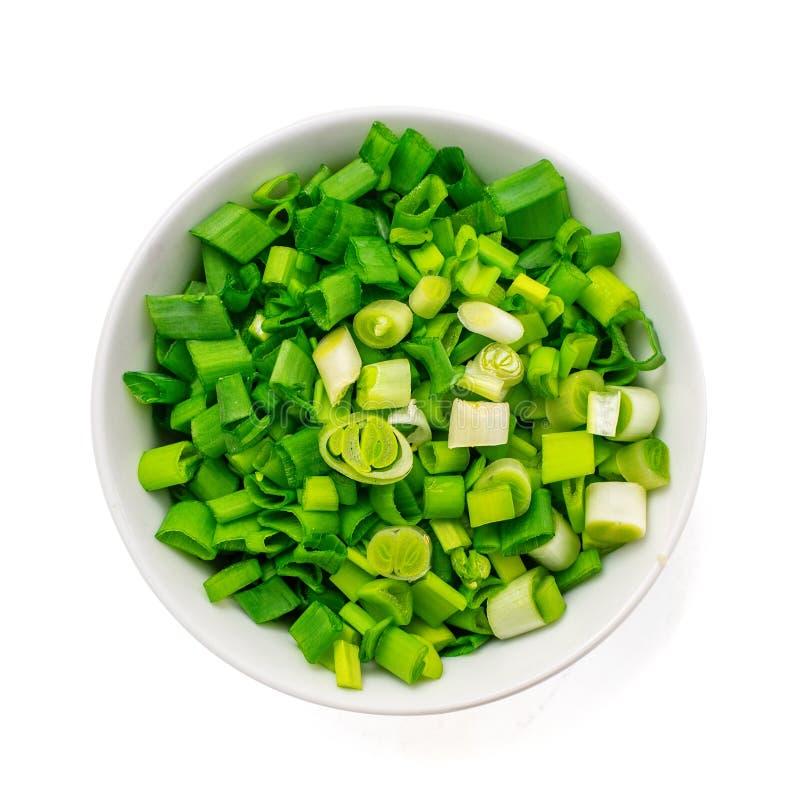 Znakomicie - siekać świeże zielone cebule w rodzajowym ceramicznym pucharze odizolowywającym na bielu Odgórny widok zdjęcia stock