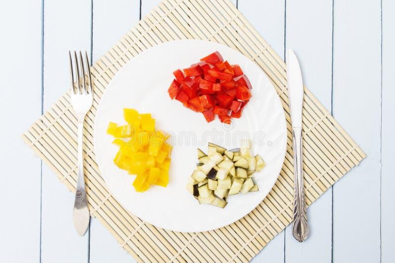 Znakomicie - siekający egplant dla jarskiego jedzenia na drewnianym tle i Bambusa mata, nóż i rozwidlenie na stole, Odgórny widok obrazy royalty free