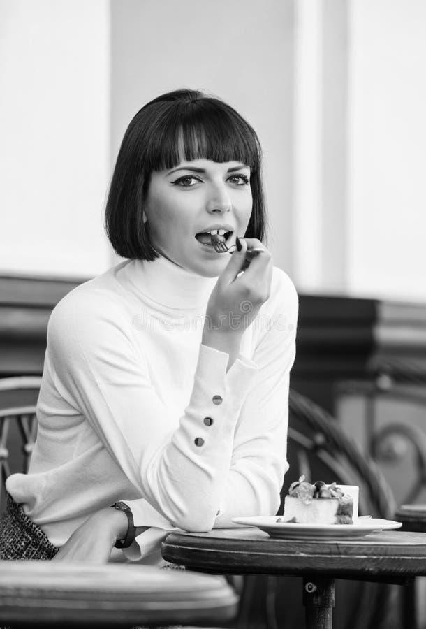 Znakomity smak Dziewczyna relaksuje kawiarni z tortowym deserem Kobiety atrakcyjna elegancka brunetka je smakosz kawiarni tortowe obrazy royalty free